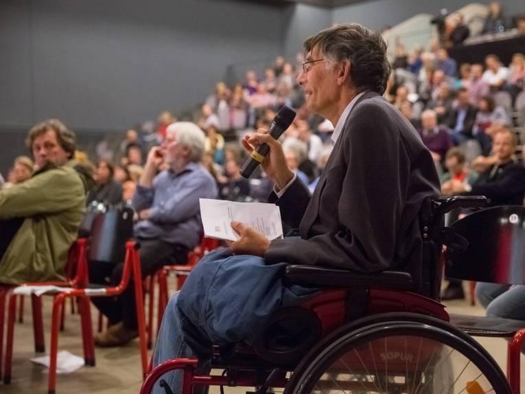 Ein Veranstaltungsteilnehmer befragt die Anwesenden auf dem Podium
