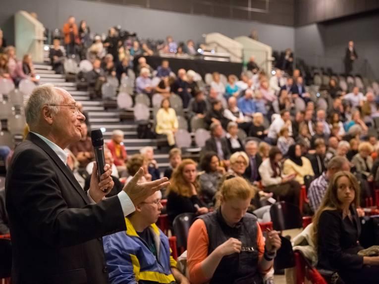 Ein Besucher befragt die Anwesenden auf dem Podium