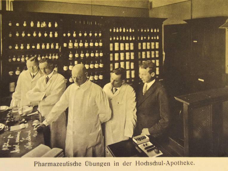 Vier Männer betrachten einen Tisch in einer historischen Apotheke, Schwarz-Weiß-Aufnahme