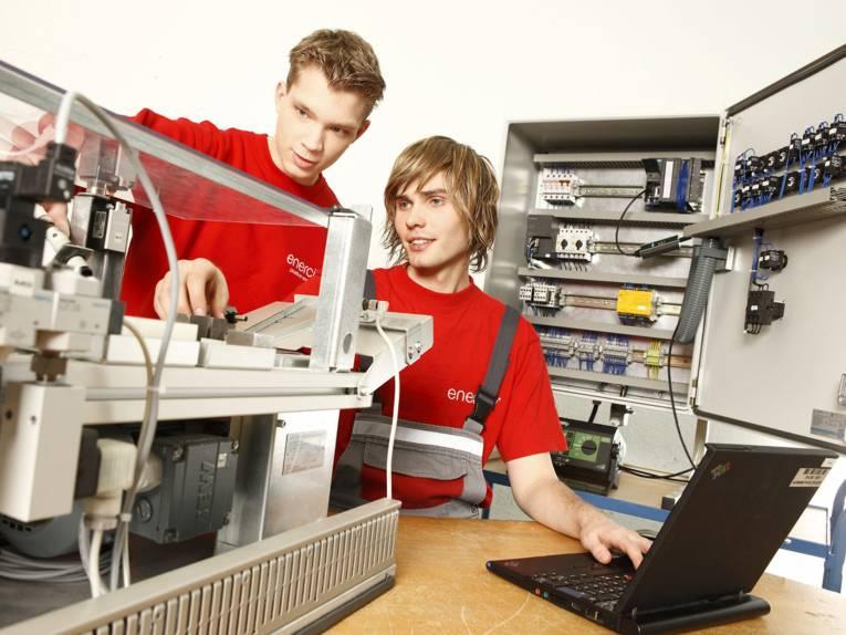 Zwei junge Männer mit Laptop und technischen Geräten