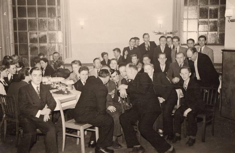 Männer und Frauen an Tischen sitzend (Schwarz-Weiß-Fotografie)