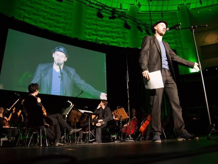 Ein Mann steht auf einer Bühne und spricht in ein Mikrofon.