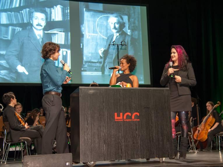 Ein Mann und zwei Frauen stehen auf einer Bühne, alle halten Mikrofone. Im Hintergrund sind Musikerinnen und Musiker eines Orchesters, auf der Leinwand sind zwei Fotografien bedeutender Wissenschaftler.