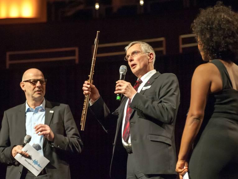 Zwei Männer und eine Frau stehen auf einer Bühne, der Mann in der Mitte spricht in ein Mikrofon und hält eine Querflöte in der anderen Hand.