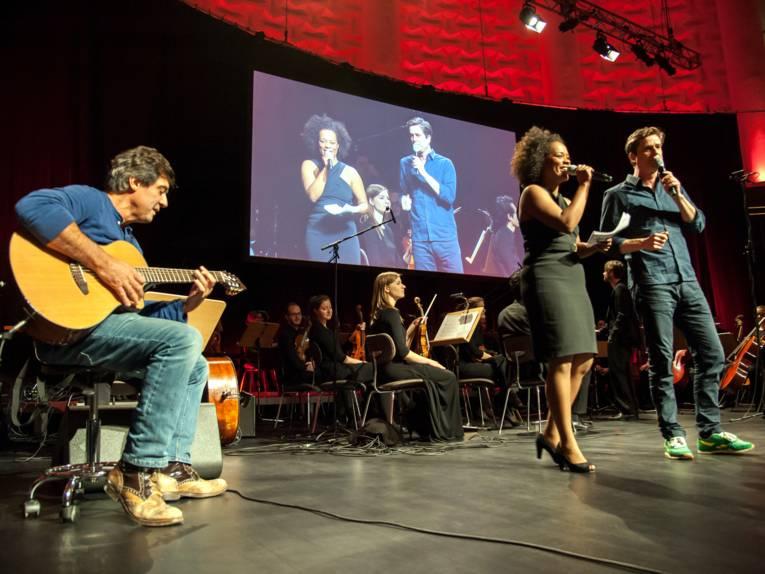 Musikerinnen und Musiker musizieren auf einer Bühne.