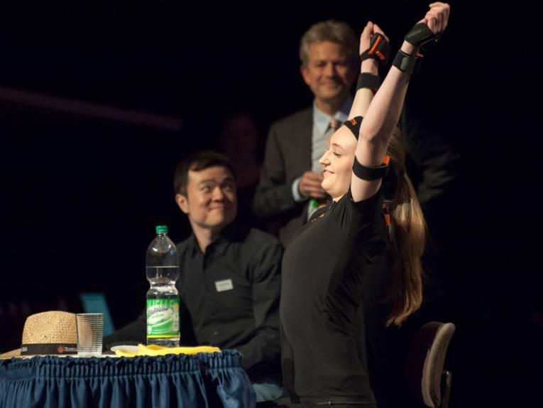 Eine Sportlerin streckt sich auf der Bühne, auf dem Tisch vor ihr sind ein Strohhut, ein Wasserglas und eine Wasserflasche.