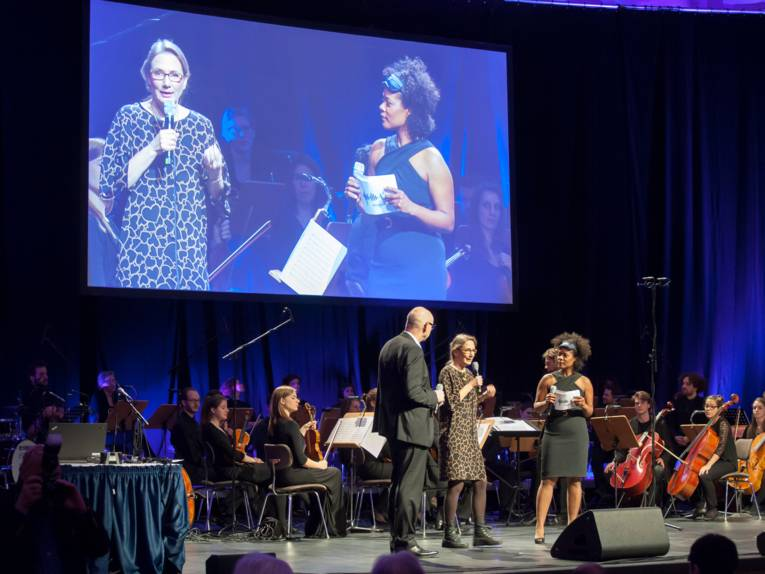 Blick auf die Bühne im Kuppelsaal, die Leinwand zeigt eine Live-Aufnahme des Bühnenprogramms.