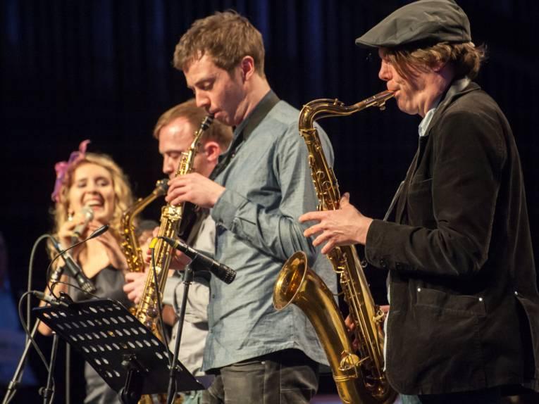 Musiker spielen ihre Instrumente, darunter Saxophone.