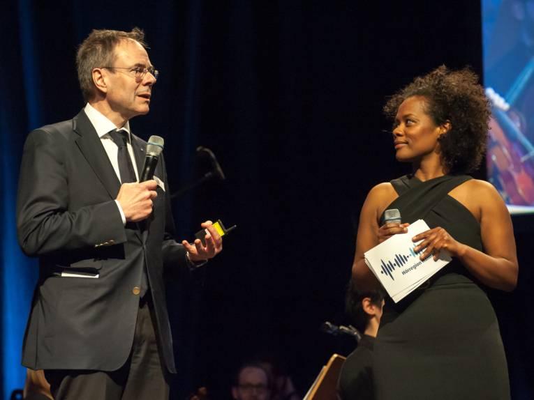 Ein Mann (links) und eine Frau stehen auf einer Bühne, beide haben ein Mikrofon in der Hand. Die Frau hält außerdem weiße Moderationskarten mit Logo der Hörregion Hannover.