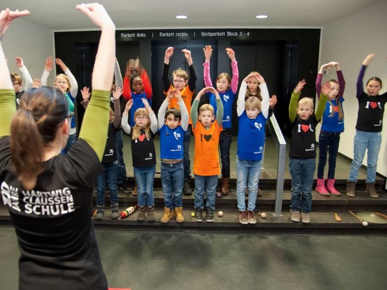 Eine Frau steht vor einer Gruppe von Kindern. Sie macht etwas vor, die Kinder machen es nach.