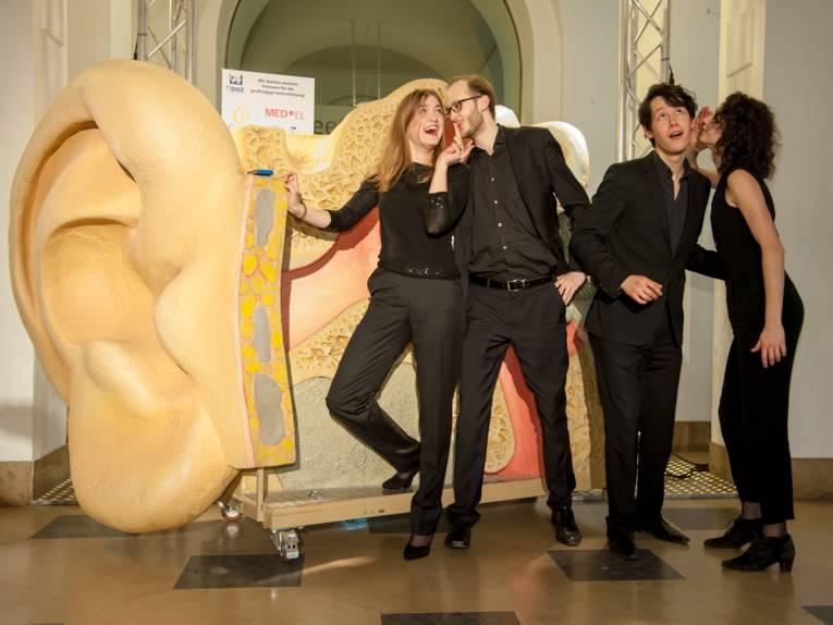 Zwei Männer und zwei Frauen stehen vor dem Modell eines Ohres und Gehörgangs. Das Modell ist ungefähr so groß wie die vier Personen.