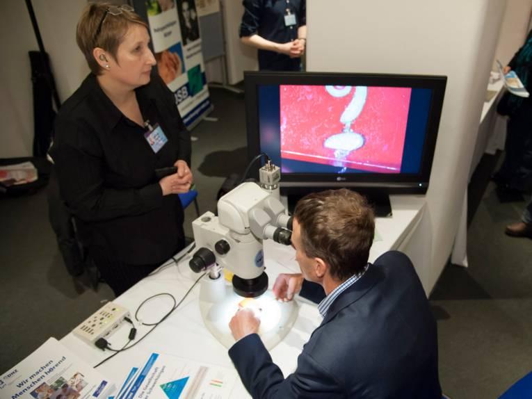 Ein Mann schaut an einem Informationsstand durch ein Mikroskop, eine Frau steht hinter dem Stand.