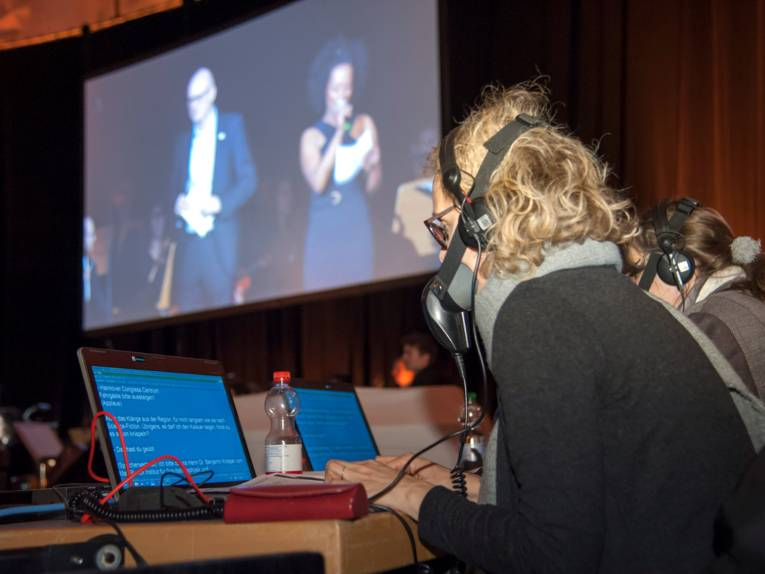 Zwei Frauen sitzen an Laptops und tragen Kopfhörer und aussenschallisolierte Mikrofone vor dem Mund.