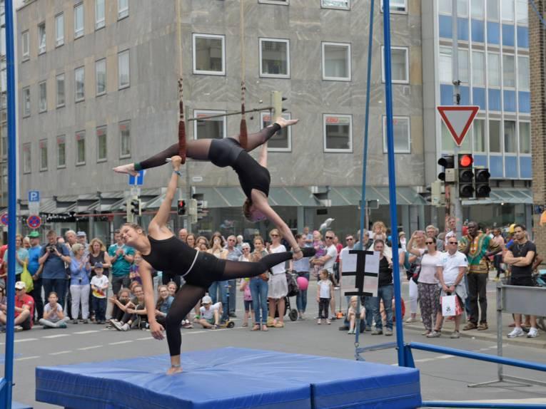 Auf einer blauen dicken Matte steht eine in schwarz gekleidete junge Frau auf einem Bein und balanciert mit ihrem rechten Arm und rechten Bein eine andere junge Frau. Die beiden werden von einer Zuschauergruppe umringt.
