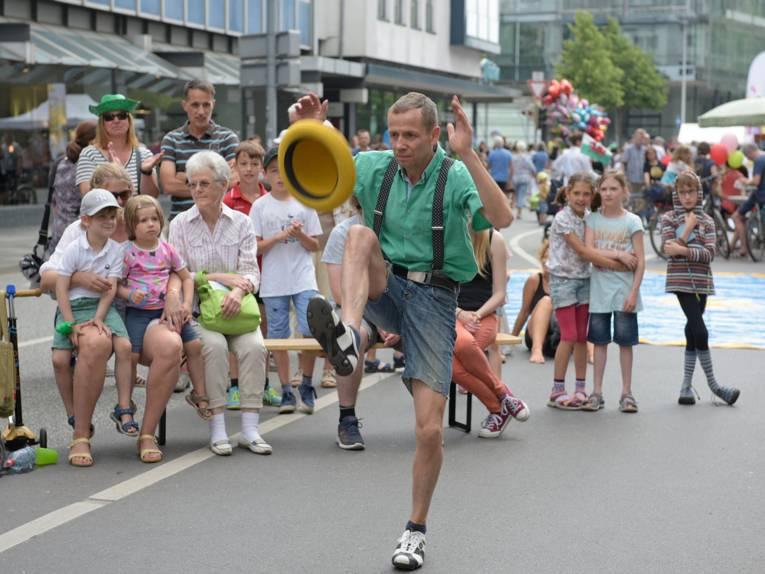 Ein Slapstick-Artist jongliert einen Hut vor staunendem Publikum.