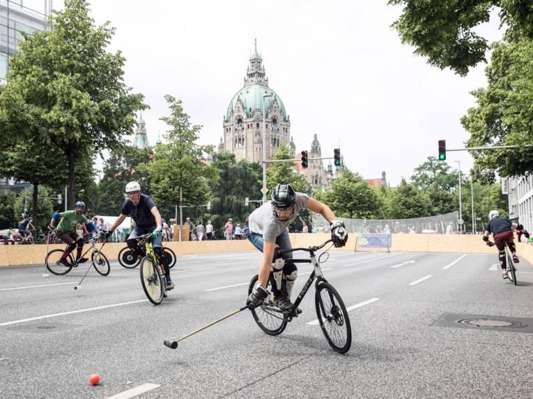 Auf einer abgesperrten Straße spielen fünf Spieler auf Fahrrädern Bike-Polo. Im Hintergrund das Rathaus von Hannover.