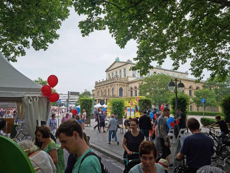 Besucherinnen und Besucher flanieren auf der Georgsstraße, die am Autofreien Sonntag für den Kraftfahrzeugverkehr gesperrt ist. Im Hintergrund das Opernhaus.