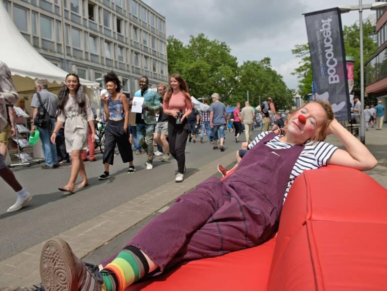 Eine Clownin liegt auf einem sehr langen roten Sofa in der Sonne, während Passanten vorbeigehen.