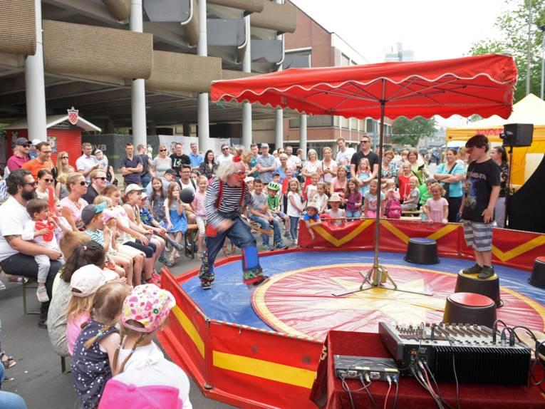 Umringt von Zuschauerinnen und Zuschauern belustigt der Clown Fidolo und sein Assistent sein Publikum, das sich vor dem Parkhaus an der Osterstraße versammelt hat.