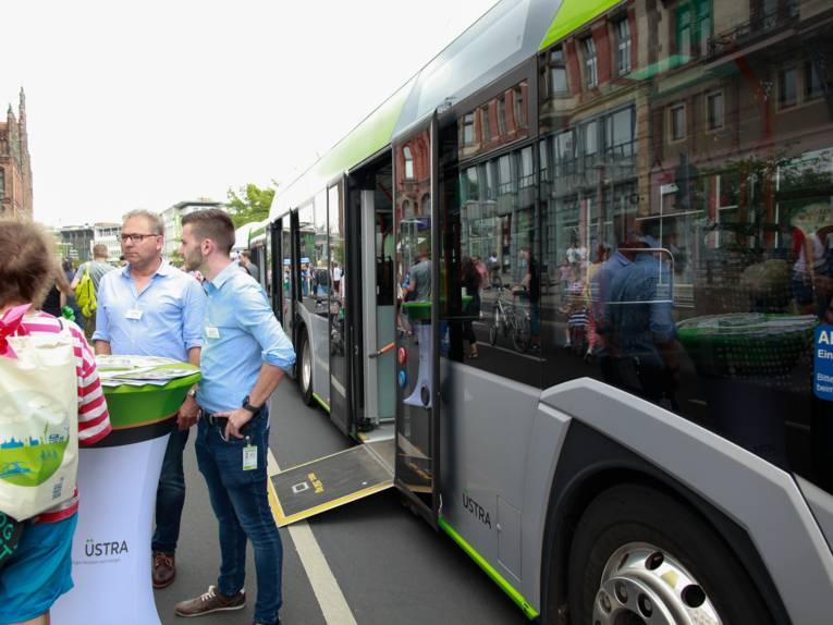 Neben einem Elektrobus, dessen heruntergeladene Rampe zum Hereinrollen einlädt, stehen zwei Männer und informieren eine Interessentin über E-Mobilität.