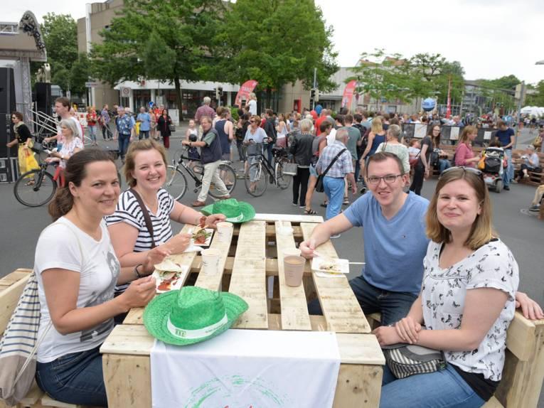 Ein aus Holzpaletten gebauter Tisch wird von drei Frauen und einem Mann als Ort für einen Imbiss genutzt. Im Hintergrund schieben Fahrradfahrer ihre Räder vorbei und flanieren Besucherinnen und Besucher.