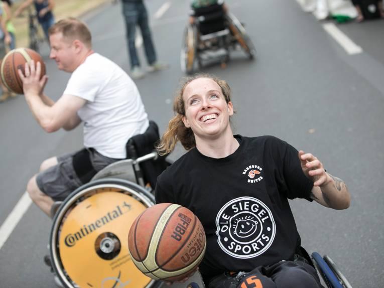 Eine Frau im Rollstuhl mit einem strahlenden Lächeln hält einen Basketball in der rechten Hand; im Hintergrund ein Mann mit einem Basketball, ebenfalls im Rollstuhl agierend, auf einer Straße.