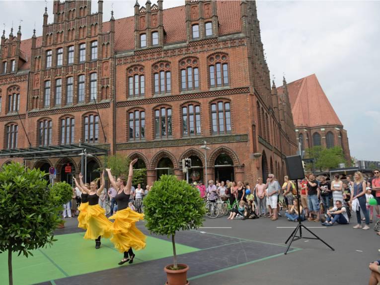 Drei Tänzerinnen auf der Straßenbühne vor dem Alten Rathaus in Hannover sind von Zuschauerinnen und Zuschauern umringt.
