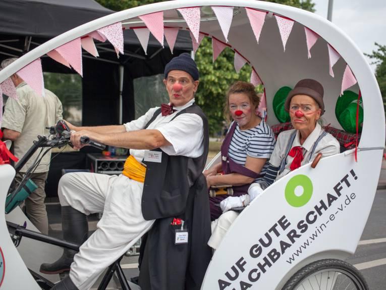 Drei als Clowns bekleidete Personen sitzen in einem offenen Gefährt, das durch Pedalkraft angetrieben wird.