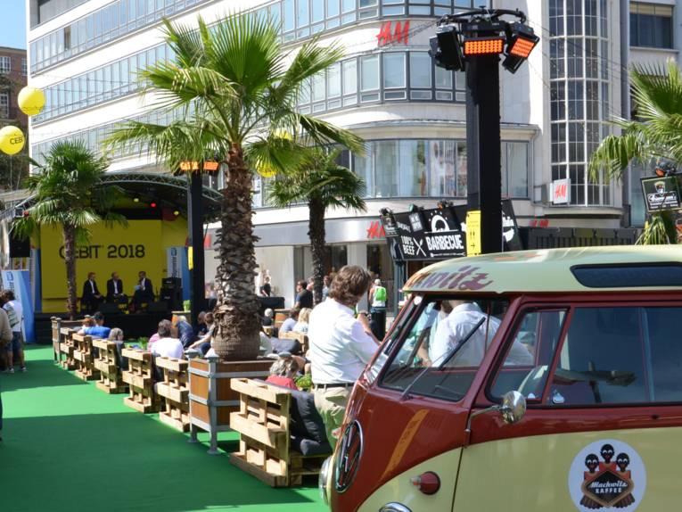VW-Bus und kleine Bühne auf einem öffentlichen Platz