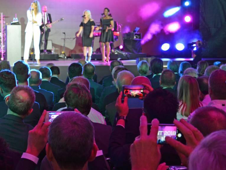 Drei Frauen auf einer Bühne, eine singt in ein Mikrofon