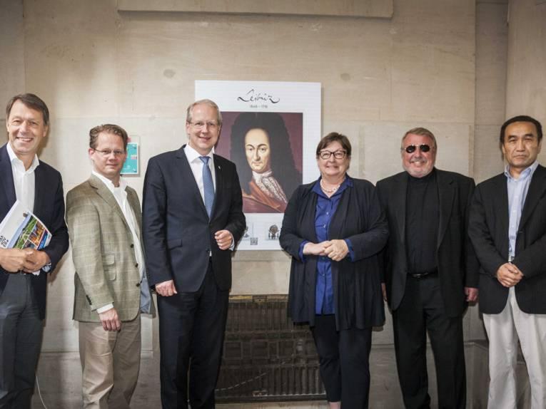 Fünf Männer und eine Frau vor einer Bildtafel, die an einer Wand hängt.