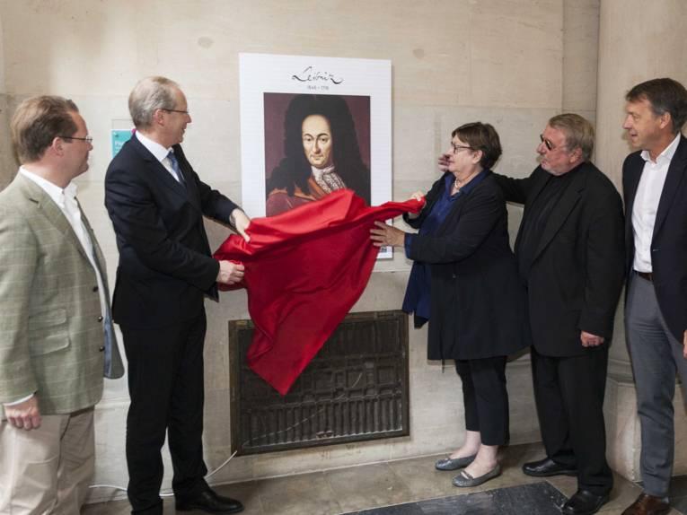 Vier Männer und eine Frau nehmen ein rotes Tuch von einer an der Wand hängenden Bildtafel herunter.
