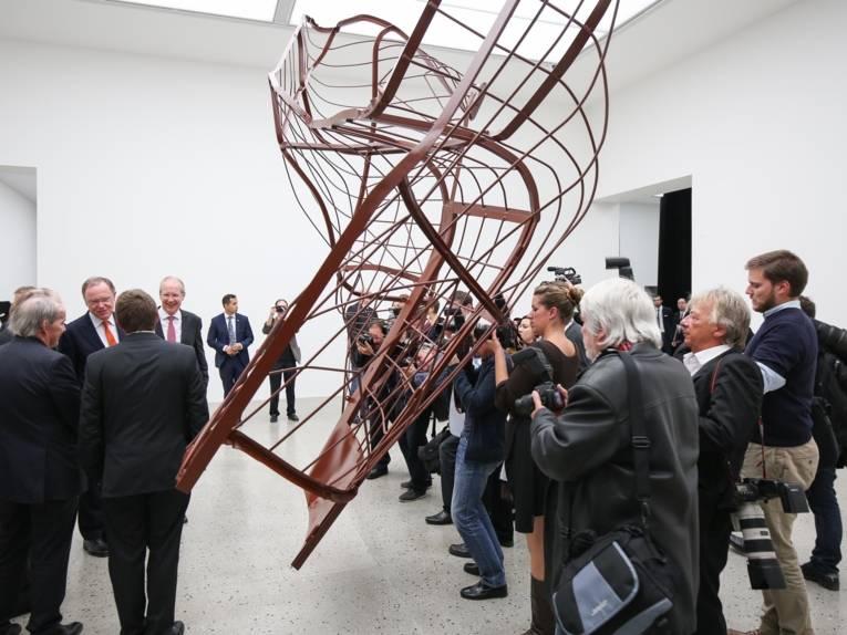 Die geladenen Besucherinnen und Besucher schauen sich das erste Kunstobjekt im Erweiterungsbau an