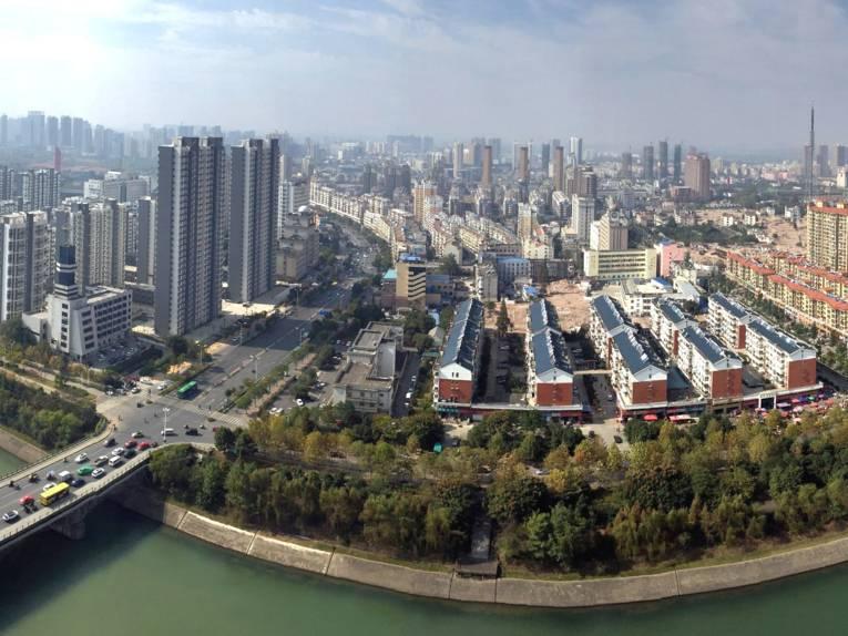 Blick aus der Vogelperspektive auf eine Stadt mit Wolkenkratzern und einem Fluss.