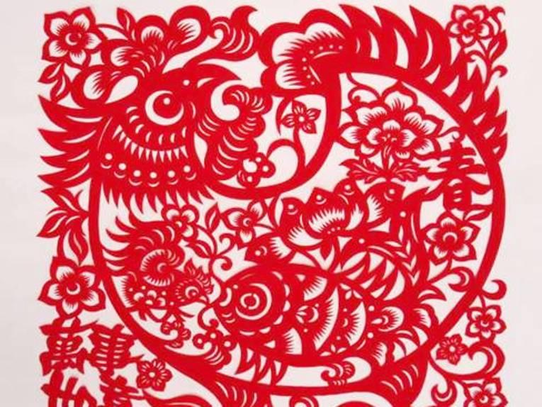 Mit einer Schere sind Stücke aus rotem Papier ausgeschnitten, dadurch ergeben sich Figuren und Muster.