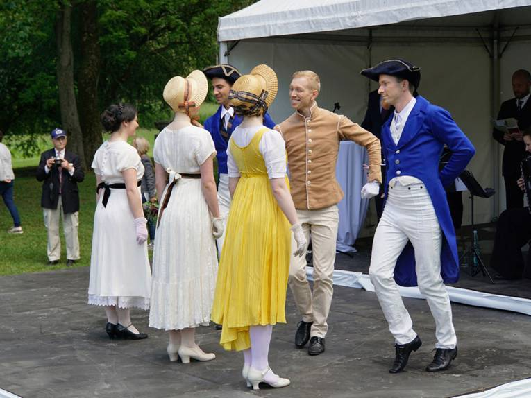 Historisch gekleidete Männer und Frauen in einer Parkanlage.