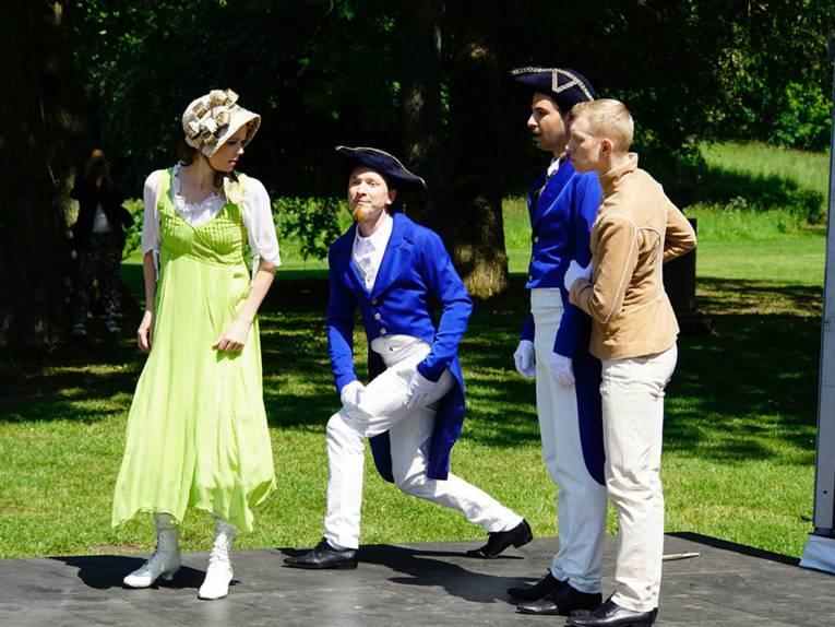 Historisch gekleidete Männer und Frauen in einer Parkanlage