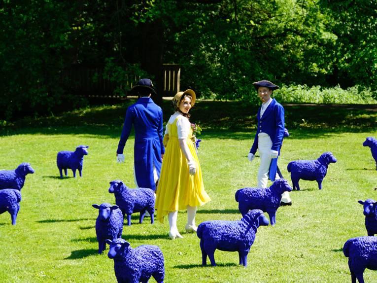 Historisch gekleidete Männer und Frauen in einer Parkanlage mit blauen Schafsmodellen
