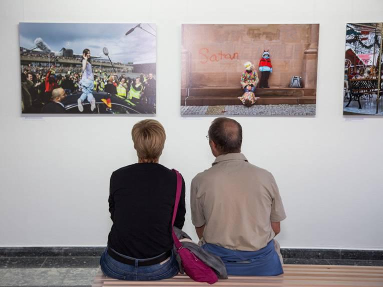 Ein Mann und eine Frau sitzen auf einer Bank und blicken auf Fotgrafien, die an der Wand hängen.