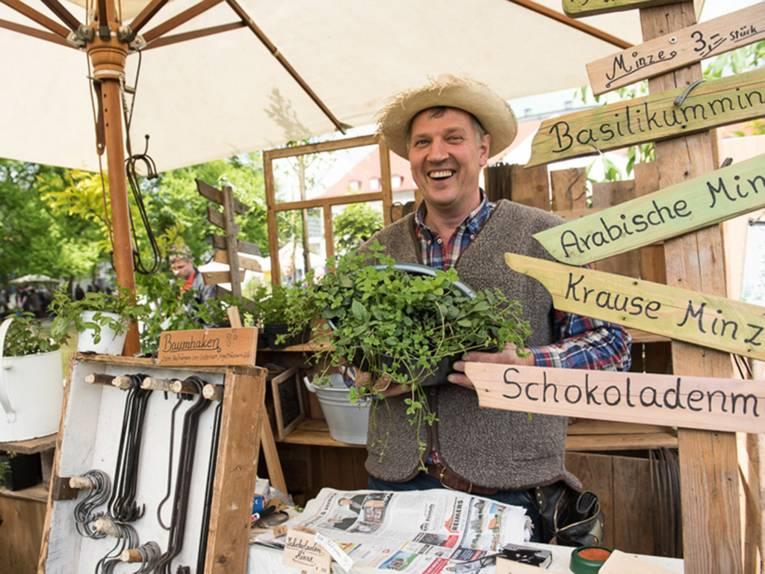 Ein lachender Verkäufer mit Weste und Strohhut hält eine Minz-Pflanze in der Hand, während zahlreiche Holzschilder rechts auf die verschiedenen Minzsorten aufmerksam machen