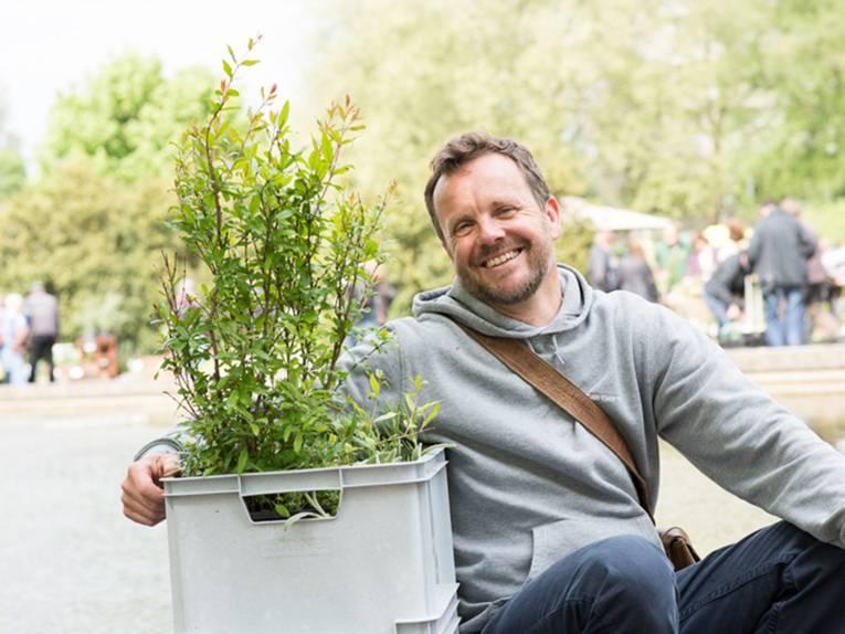 Ein fröhlicher Mann hält eine Plastikbox mit Pflanzeneinkäufen