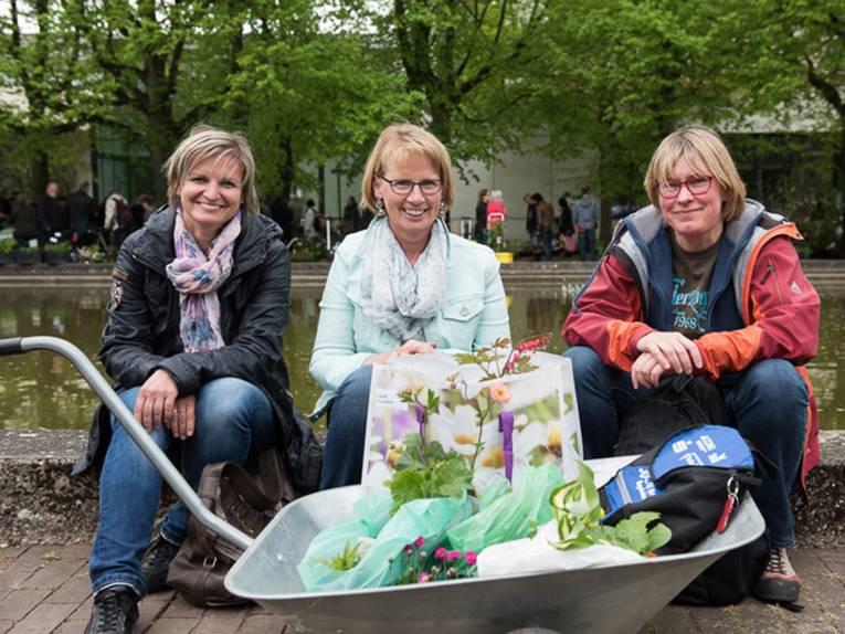 Drei Besucherinnen sitzen auf einer Teichumrandung und haben vor sich eine mit Pflanzeneinkäufen gefüllte Karre