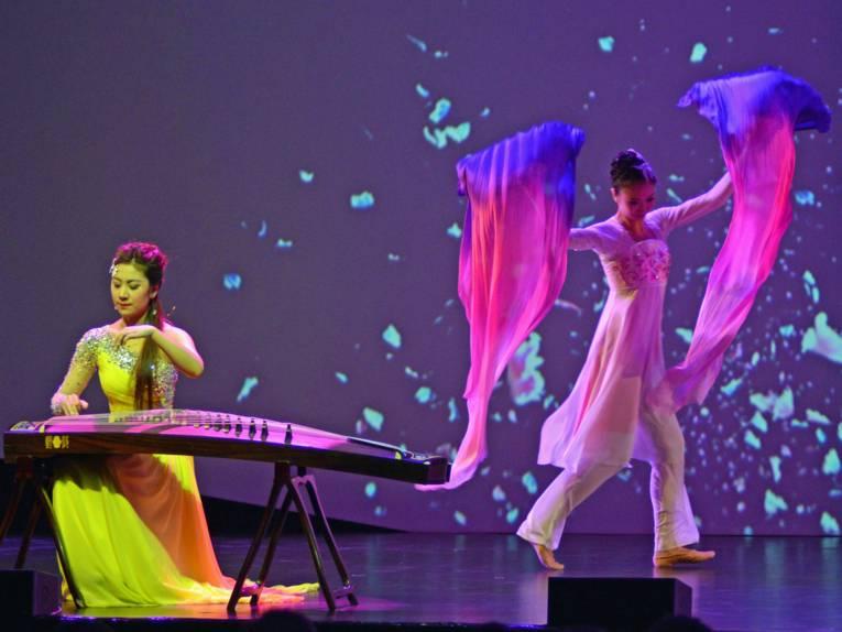 Musikerin und Tänzerinnen auf einer Bühne.