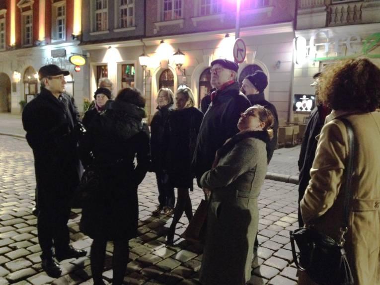 Mehrere Personen stehen beieinander und schauen sich die drumherum stehenden, alten Gebäude an.