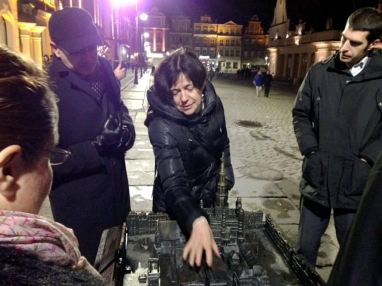 Eine Frau gibt anhand eines Modells Infos zur Altstadt Poznan.