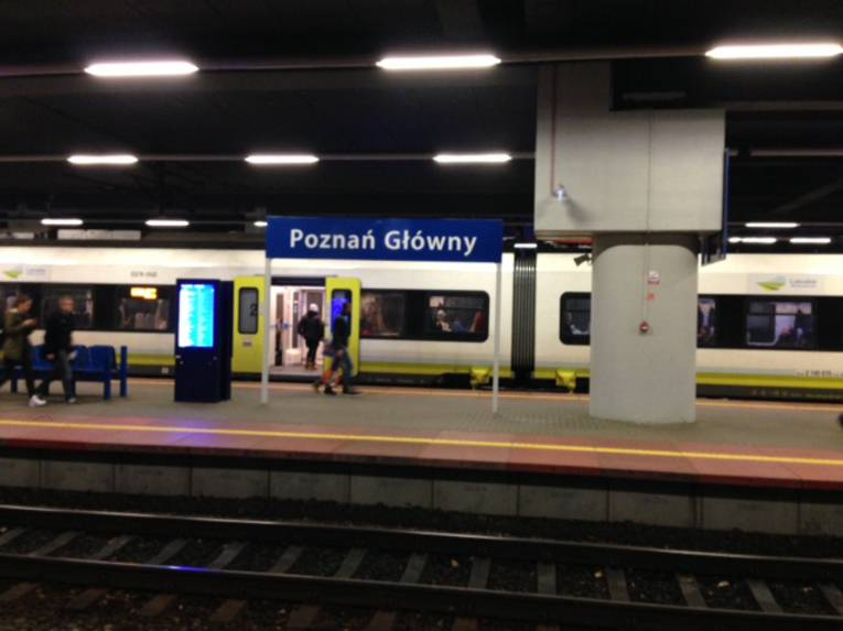"""Ein Zug hält an einem Bahnsteig, auf dem Bahnhofsschild steht """"Poznań Główny"""""""