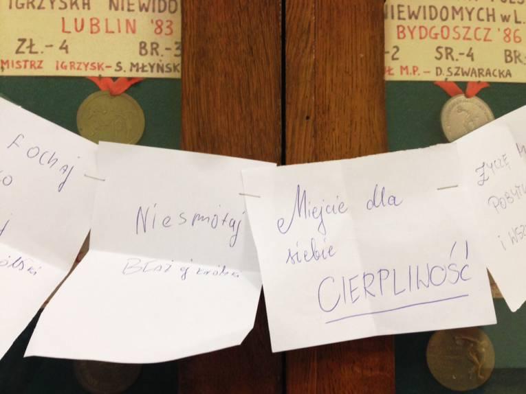 An den Türen einer Vitrine mit Medaillen hängen mehrere weiße Zettel. Auf den Zetteln stehen handgeschriebene Worte in polnischer Sprache.