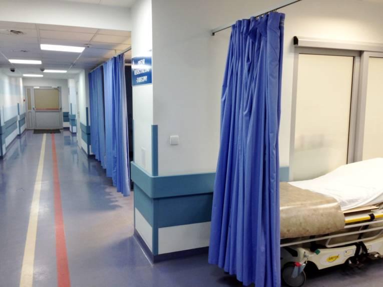 Krankenhausflur, Vorhänge trennen Nischen ab.