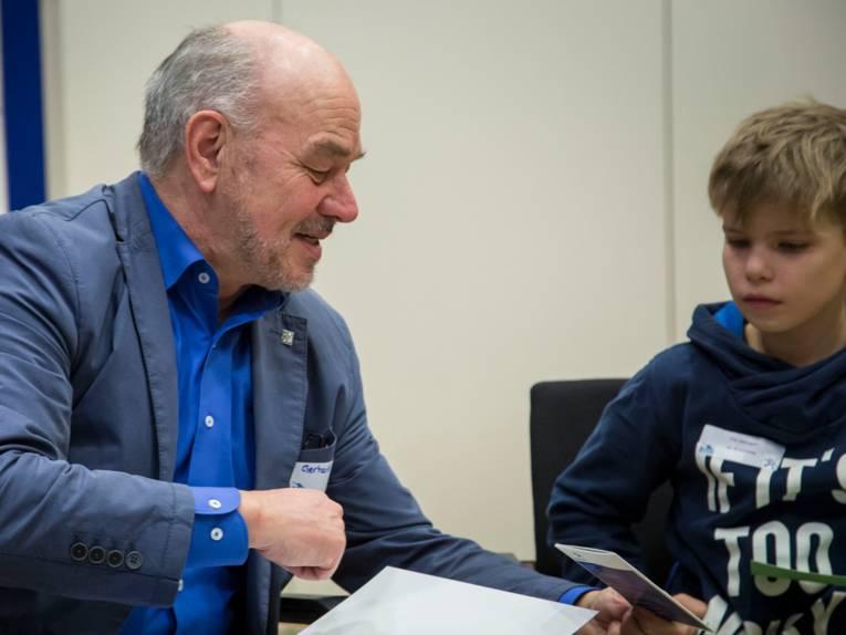 Ein Mann sitzt mit einem Jungen beisammen und erklärt etwas anhand von Unterlagen.
