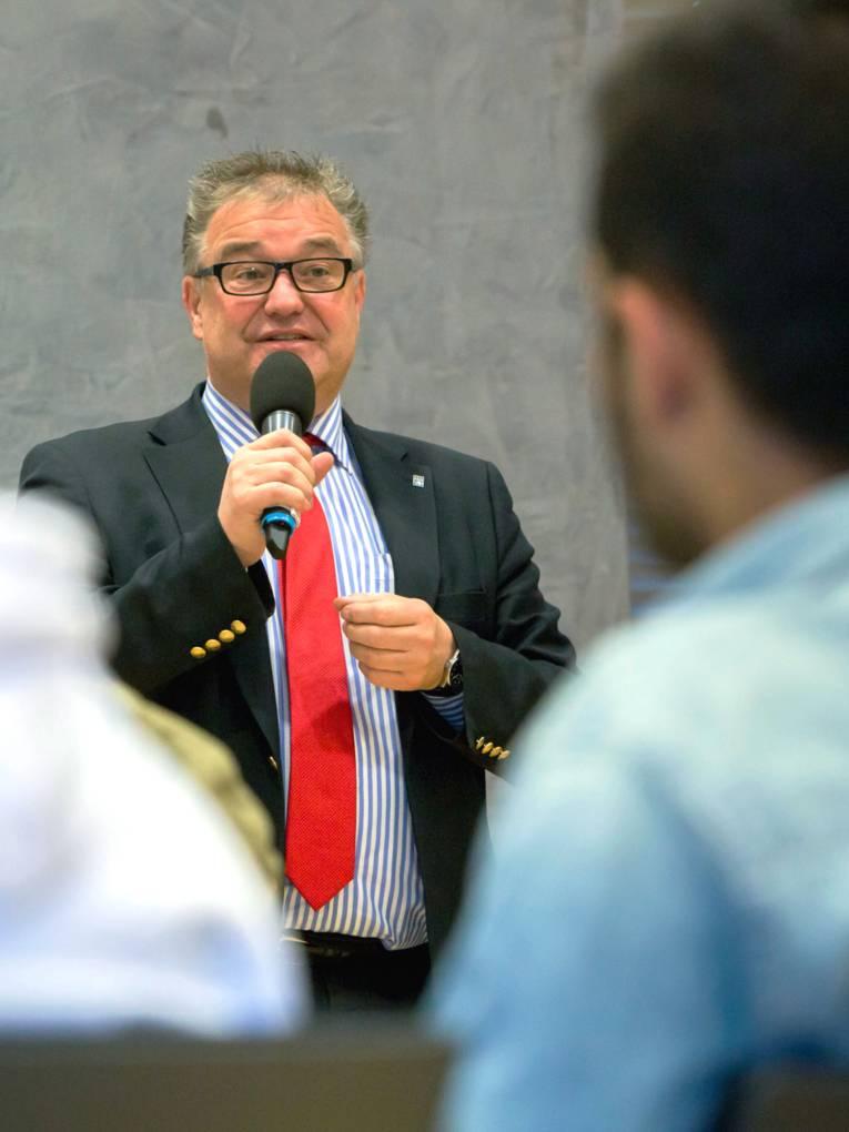 Aus der Perspektive der Zuhörerinnen und Zuhörer: Ein Mann trägt einen Anzug und spricht in ein Mikrofon, das er in der rechten Hand hält.
